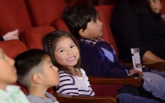 Child in audience of Civic Theatre, smiling at camera