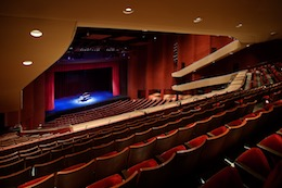 Photo of the San Diego Civic Theatre stage, with empty seats in the foreground and a grand piano on stage